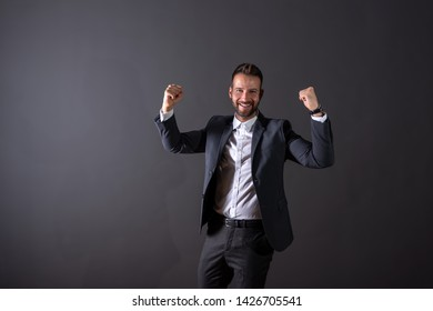 A cheering handsome young businessman in a suit standing in front of a dark grey background in a studio.