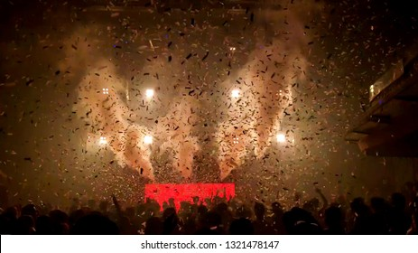 Cheering happy joyful crowd with raised hands, falling confetti at concert,music festival. Abstract Background of Party Concert.Crowd happy and joyful in club.Blur image of concert,Celebration party.