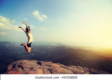 cheering happy young asian woman jumping on mountain peak cliff edge