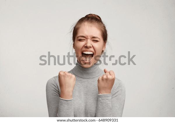 Fröhliche junge kaukasische Frau mit reiner Haut und schönem Aussehen klammerende Fäuste, die vom Erfolg begeistert sind. Freudenreiche Frau schreit mit Glück, um ihre Ziele zu erreichen. Glücksspiel