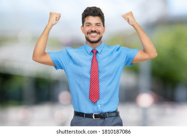 Cheering hispanic businessmann with beard and tie outdoor in summer in city