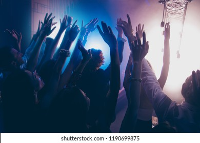 Cheering live shine show performance concept. Crowd shadow of people at during a concert dancing in party club with neon lights raised hands up background