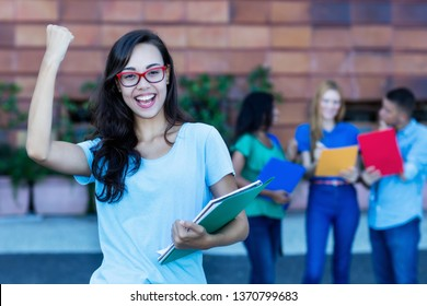 Cheering nerdy french female student with group of students outdoor in the summer in the city