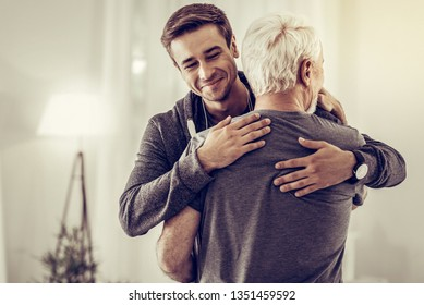 Cheering up sick dad. Smiling beaming handsome young man in grey hoodie embracing grey-haired dad in years cheering him up