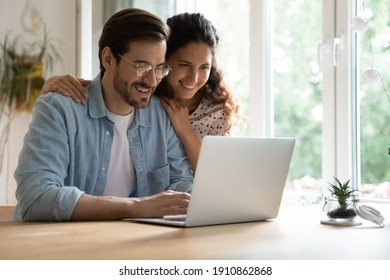 Cheering spouses having warm relations hug by desk at home make shopping purchases online at web store. Friendly young couple in love look at computer screen planning wedding choosing tour on vacation