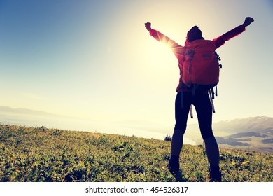 cheering successful woman backpacker open arms on mountain peak