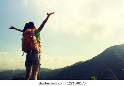 Cheering woman backpacker enjoy the view at mountain peak