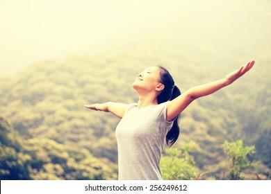 cheering woman enjoy the beautiful view at mountain peak