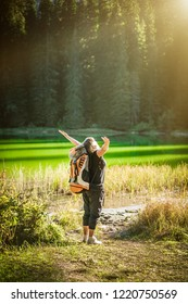 Cheering woman hiker with backpack open arms at mountain lake. Zabljak, Montenegro