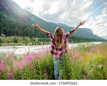 Cheering woman open arms at sunrise in wild flowers field by the river ,Nature of Life female embracing freedom
