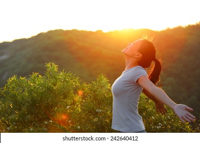 cheering woman open arms at sunrise mountain peak wellness concept
