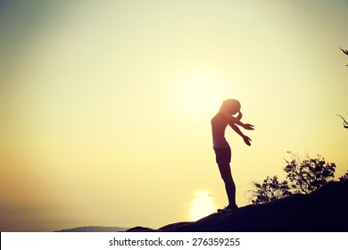 cheering woman open arms at sunset mountain top cliff edge