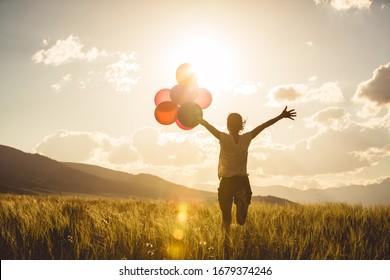 Junge asiatische Frau auf Grasland mit farbigen Ballons bejubeln