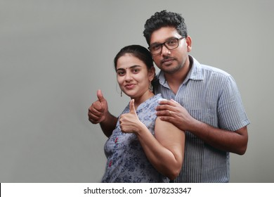 Cheering Young couple shows thumbs up sign
