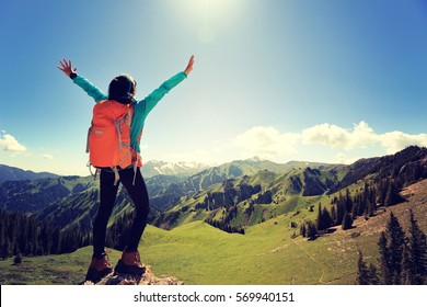 cheering young woman backpacker hiking on forest mountain peak