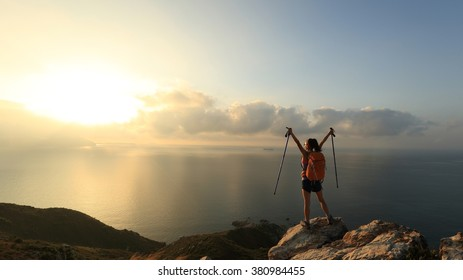 cheering young woman backpacker at sunrise seaside mountain peak