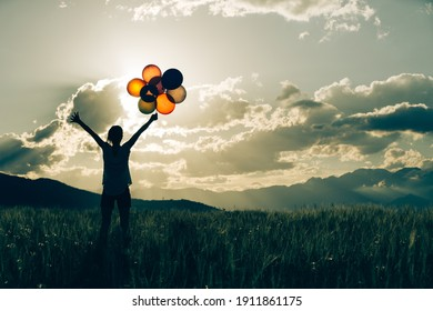 Cheering young woman with colored balloons on sunset grassland