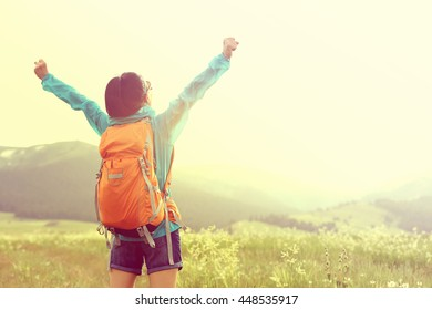 cheering young woman hiker open arms to snow mountains in the distance