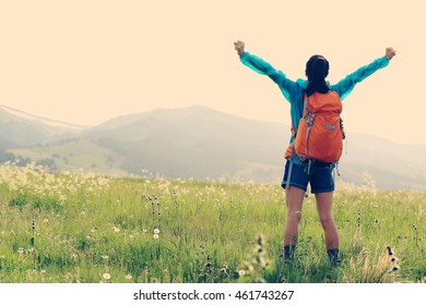 cheering young woman hiker open arms in grassland