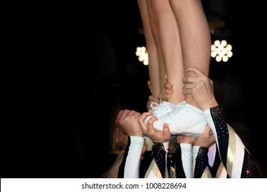 Cheerleader's legs and feet being held up between spotlights