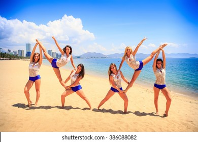 cheerleaders in white blue uniform perform double Heel Stretch on sand beach smiles against sea wind shakes long hair