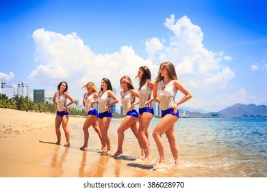 cheerleaders in white blue uniform stand in line with hands on hips in shallow water against resort wind shakes hair