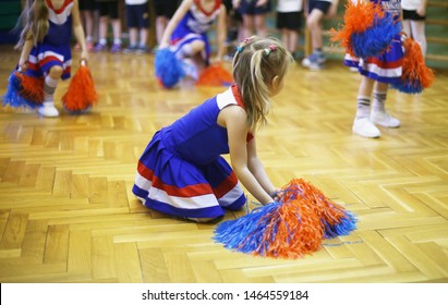 Cheerleading class in school in a sport hall. Back to school activities. Children education and development. Cheerleaders in blue, red and white dresses are dancing on parquet floor of sport hall.