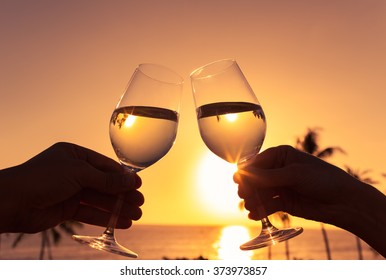 Cheers against a sunset.