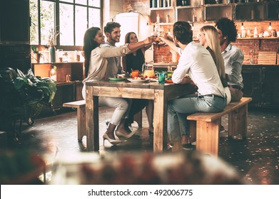Cheers to the best friends! Group of cheerful young people cheering with champagne flutes and looking happy while while sitting at the dinning table together