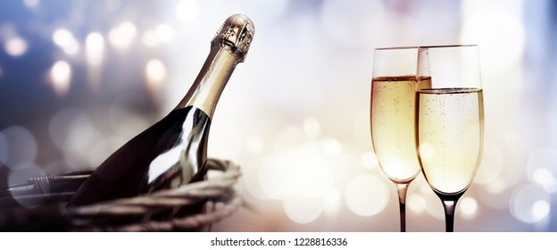 Cheers with a bottle of champagne for a new year on bokeh background