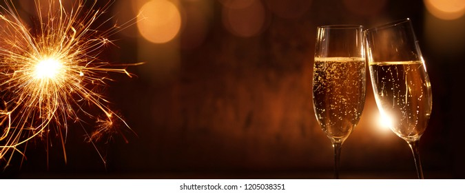 Cheers with champagne for happy new year on festive background with sparkler and golden bokeh