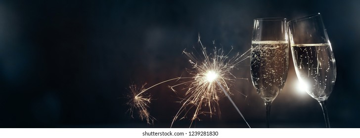 Cheers with champagne for happy new year on dark blue  background with sparkler