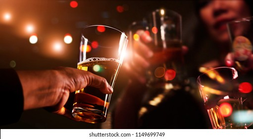 Cheers clinking of friends with beer drink in party night after work on colorful blur  background, Group of young people happy having fun together with friendship.