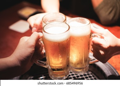 Cheers, clinking glass mug of beer hanging out with your friends in a bar