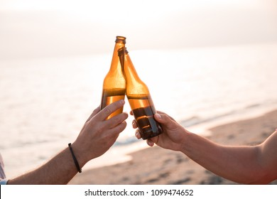 Cheers! Close up of hands toasting with bottles of beer in the beach. Celebration concept