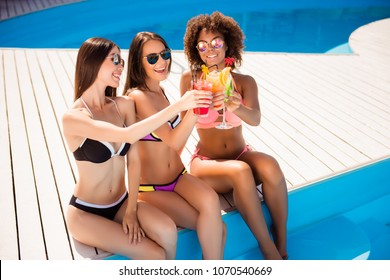 Cheers! Close uo of three girlfriends sun bathing near the pool. Attractive skinny chics in colorful swimming suits, in trendy eyewear, with juices, so hot and elegant, cheerful and delicate