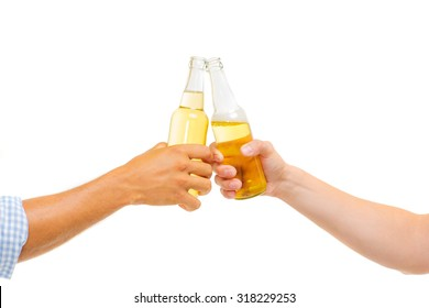 Cheers! Closeup of hands toasting with bottles of beer. Isolated on white.