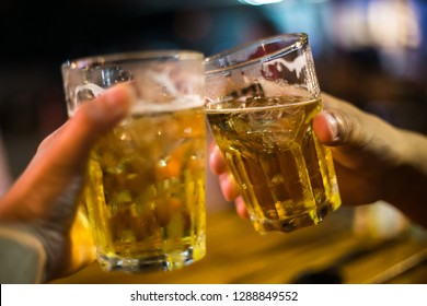 Cheers. Close-up picture of two friends holding beer glass and clinking together.