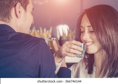 Cheers! Couple in love is drinking alchool togheter in a shot glass during a party - caucasian people - people, drink, party and lifestyle concept