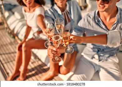 Cheers! Cropped image of group of friends relaxing on luxury yacht and drinking champagne. Having fun together while sailing in the sea. Traveling and yachting concept.