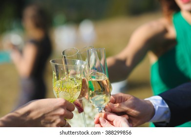 Cheers. friends celebrating a wedding  party and clinckind glasses of champagne or wine, outdoors.