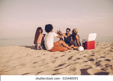 Cheers to friends! Cheerful young people spending nice time together while sitting on the beach and drinking beer