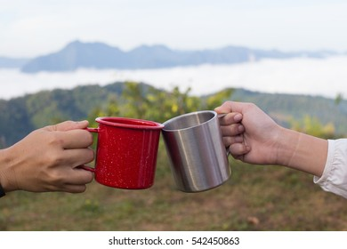 Cheers glass by camping people together at their camping site at the mountain top with a sea of fog view
