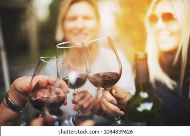 cheers with glasses of red wine, friends in the restaurant