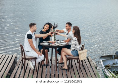 Cheers! Group of friends enjoying outdoor picnic in river pier. Friendship, food and fun concept