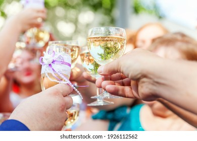 Cheers. Group of people drinking and toasting in restaurant. Hands holding glasses of champagne and wine making toast. Christmas new year wedding holiday party time. Celebration and nightlife concept