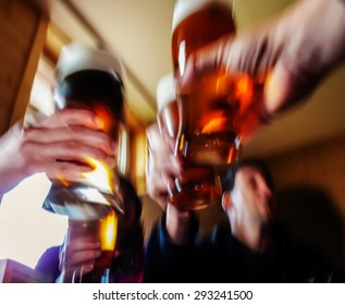 cheers! - hands with glass of beer in abstract motion blurred scene
