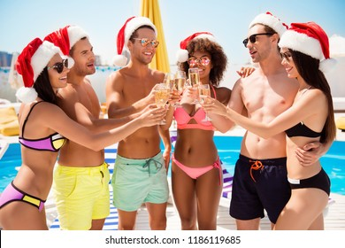 Cheers! Happy three couples are toasting with drinks, wearing santa caps, sun, fun, vacation mode, luxury swim and eye wear, tourist resort, blue clear sky, love in air, wine in glasses, new year!