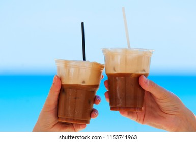 Cheers, ice cold coffee on the beach with straws, in summer