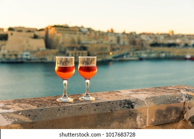 Cheers from Malta, sunset over Valletta with wine glasses